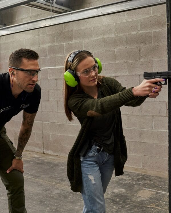 a woman being trained to shoot a gun