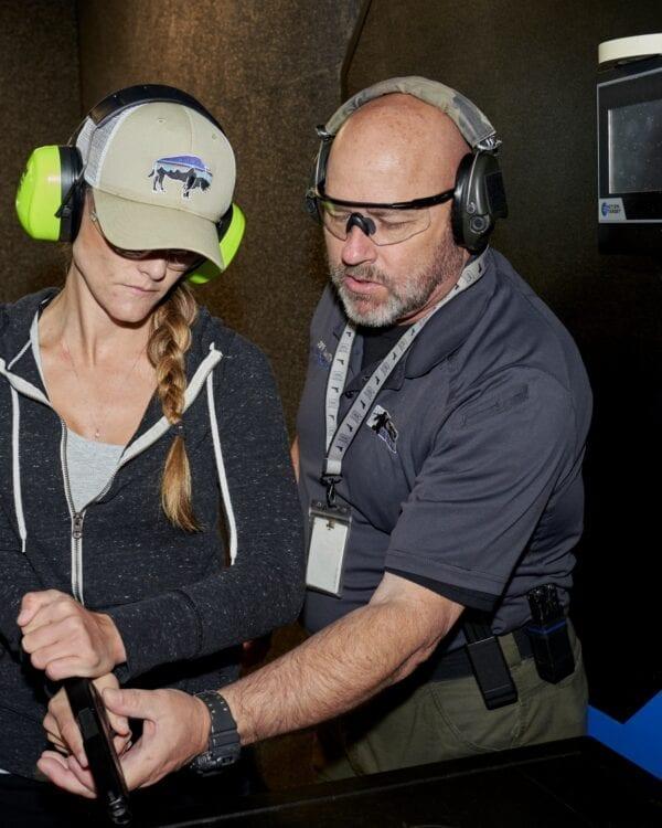 A man helping a woman train in gun use.